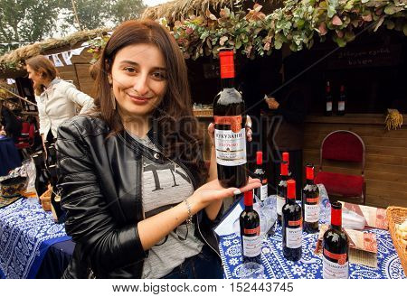 TBILISI, GEORGIA - OCT 16, 2016: Cute georgian woman showing bottles of red wine made specialy for festival Tbilisoba on October 16, 2016. Tbilisoba is traditional festival in capital of Georgia from 1979