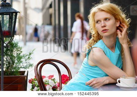 Portrait of slim young woman with wavy blond hair in blue dress sitting in cafe