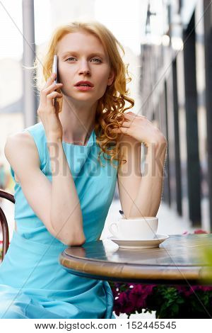 Beautiful blond woman in a blue dress talking on mobile phone in cafe outdoors
