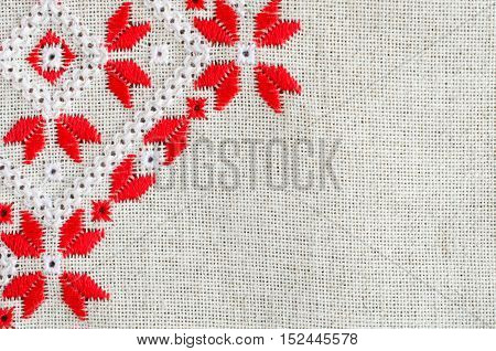Element handmade embroidery on linen by red and white cotton threads. Design of ethnic textures. Background with embroidery. Geometric ornament.