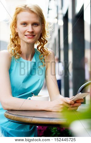 Smiling girl sitting at table in cafe and holding cellphone, the model looking into the camera