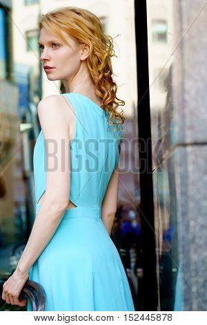Fashion portrait of model in long blue dress in half a turn
