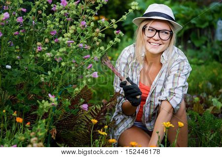 Young smiling gardener woman in hat with hoe in her hand next flowers