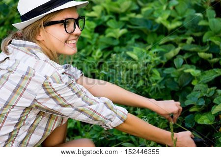 Outdoors portrait of young woman gardener in shirt and hat takes care of harvest