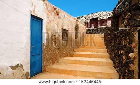Narrow street with old houses in the fishers village Puertito on the Canary Island Lobos Fuerteventura Spain.