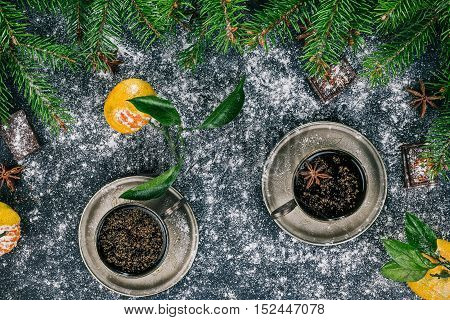 Cups of coffee over black surface covered with sugar powder and decorated with frame of evergreen twigs, tangerines, chocolate and star anise