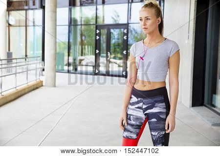 Beautiful young woman in sportswear listening to music through earphones on footpath