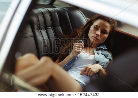 Beautiful thoughtful girl lying on back seat of car, tinted photo