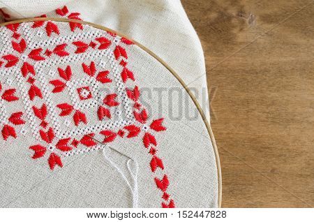 Element handmade embroidery on linen by red and white cotton threads. Craft embroidery. Design of ethnic pattern.