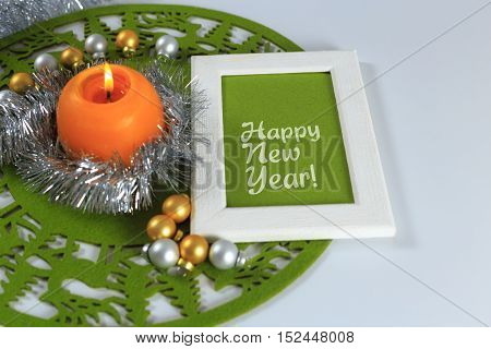 Merry Christmas and New Year greeting card on green christmas mat silver tinsel with silver and golden christmas balls and orange candle against white background horizontal top view