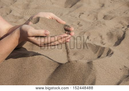 Hands strew sand,Fingers of hands and sand