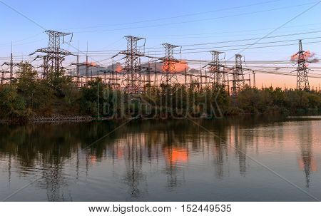Impression network at transformer station in sunrise high voltage up to pink sky take with yellow tone