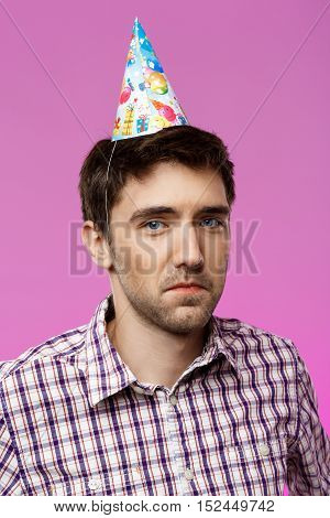 Resentful young handsome man posing over purple background. Birthday party. Copy space.