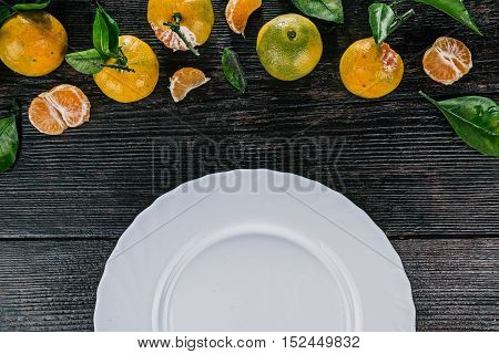 Top framework of mandarins with green leaves over dark wooden surface