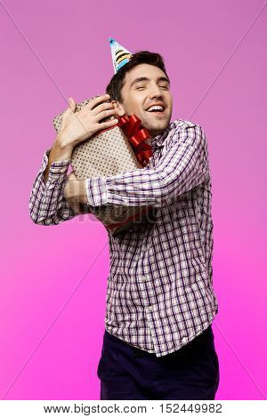Happy young handsome man embracing birthday gift in box over purple background. Copy space.