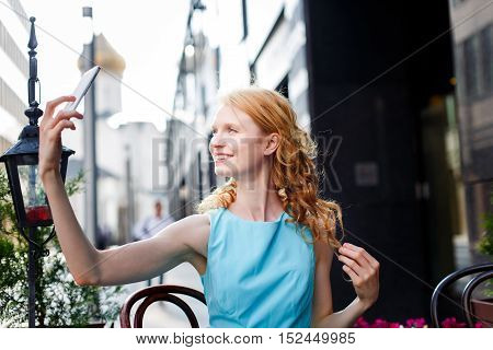 Young curly blond woman in blue dress sitting in cafe and takes a photo on her white smartphone