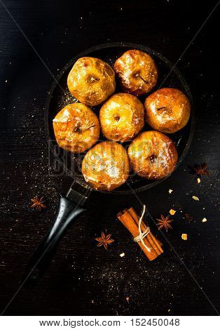 Apples baked with sugar, honey and spices, on dark wooden table. Top view