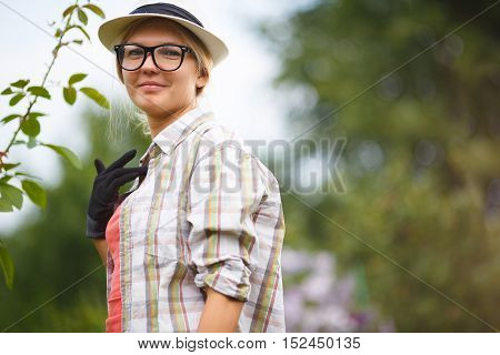 Portrait of pretty caucasian young woman in country style in work gloves on nature background