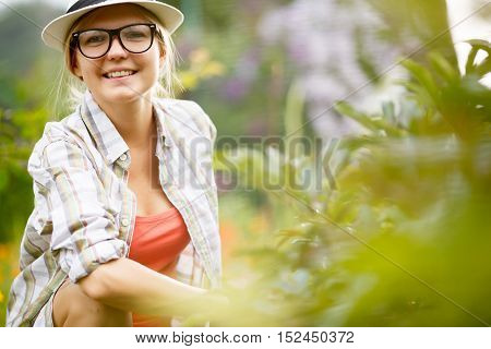 Portrait of happy smiling female gardener in hat on nature background