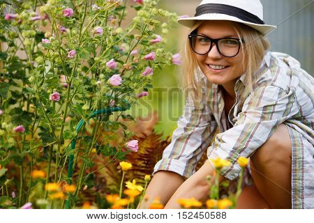 Young woman florist sitting and working in her flowers garden and looking at camera