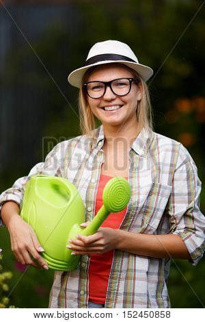 Beautiful young woman gardener holding green watering can on a nature background