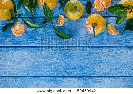 Top framework of mandarins with green leaves over painted sky-blue wooden surface
