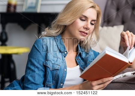 Feeling comfortable. Young sportive woman lying on floor, and leaning on couch while reading book.