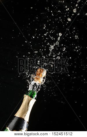 Classic champagne bottle with cork exploding, alcoholic beverage