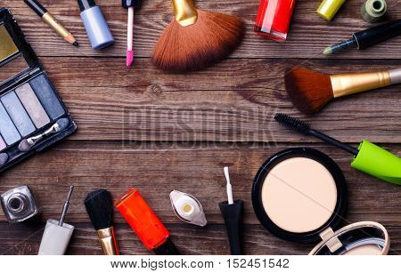 Makeup cosmetics, brushes and other essentials on brown background