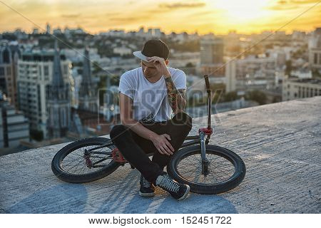 Young Handsome Hipster Man Sitting On The Roof And Posing On Bicycle On Sunset