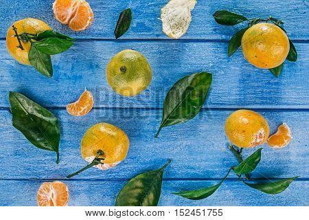 Top view of mandarins with green leaves over painted sky-blue wooden surface