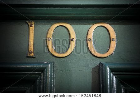 Number one hundred brass door number on weathered painted doorway
