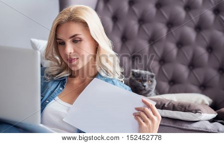 Business at home. Portrait of young blond lady using her laptop and holding paper sheet.