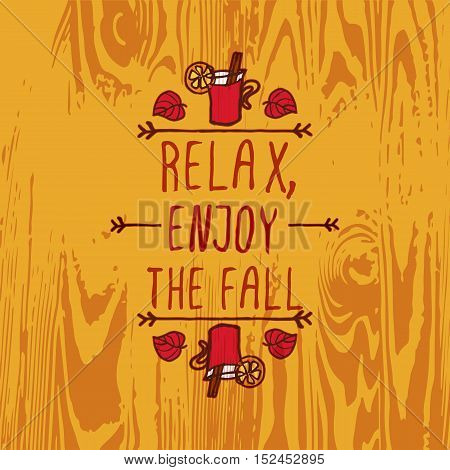 Hand-sketched typographic element with mulled wine, leaves and text on wooden background. Relax enjoy the fall