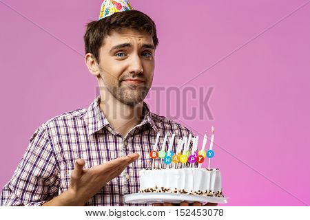 Man holding birthday cake with one not blow out candleover purple background. Copy space.