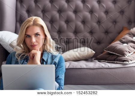 What to answer. Serious blond woman holding laptop and touching her chin with fingers on background of grey couch.
