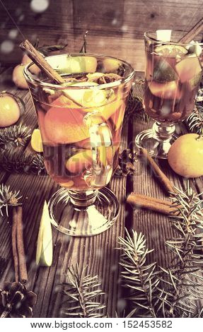 Christmas mulled wine with the addition of fragrant spices, apples, mandarins and oranges. With Christmas tree branches and pine cones. Toned