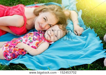 Young mother hugging her little girl lying on blue blanket on lawn in park