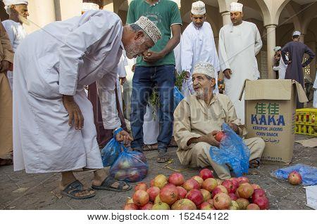 Nizwa Oman October 13th 2016: omani man selling pomegranates