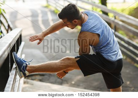 Young man doing stretching exercises in a park on a wooden bridge