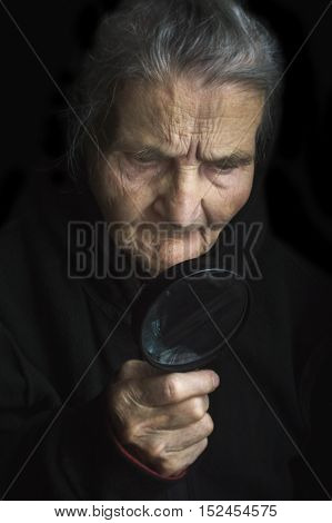 Elderly woma with magnifying glass. Selective focus.