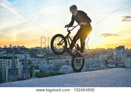 Silhouette Of A Man Doing An Jump With A Bmx Bike Against Sunshine Sky.