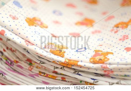 Baby swaddling with bears and hearts. Heap of folded linen of various colors. Pile of the washed and ironed linen. Stack of swaddling bands.