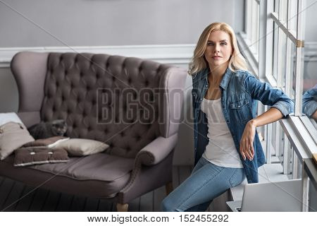 Felling comfortable. Pretty blond girl leaning on windowsill at home, on background of vintage grey couch.
