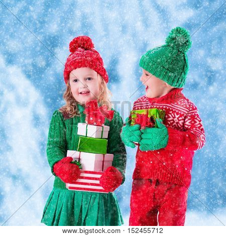 Little girl and boy in red and green knitted hat holding Christmas present boxes in winter park on Xmas eve. Kids play outdoor in snowy winter forest. Children opening presents. Toddler kids with gifts