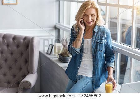 Talking to love. Happy blond woman leaning on windowsill and talking per mobile phone at home near big window.