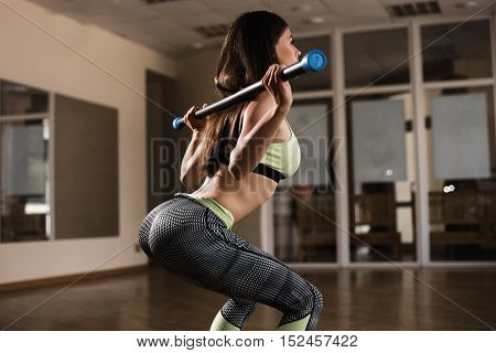 Back View Young Adult Girl Doing Heavy Duty Squat In Gym With Bodybar. Woman With Perfect Abs Doing