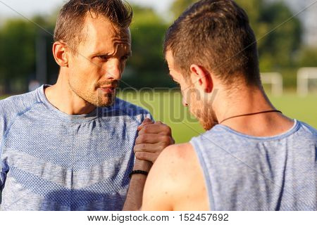 Outdoors portrait of two serious strong men shake hands before competition