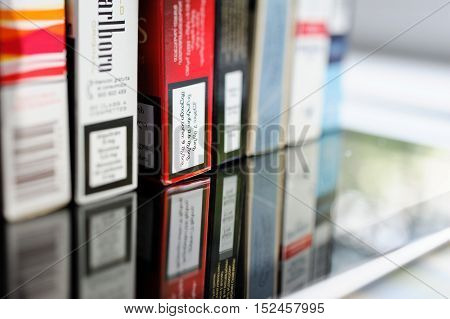 Multiple cigarettes pack on glass table with inscription regarding warning messages and the tax mark in diverse European language including Georgian Kartvelian language.