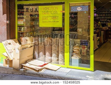 AIX-EN-PROVENCE FRANCE - JUL 17 2014: Grocery store in old city of Aix-En-Provence with people inside and special offers on windows